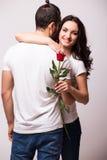 Kobieta ściska jej chłopaka i trzyma róży zdjęcie royalty free