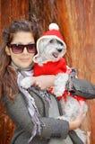 Kobieta ściska jej psa ubierał z czerwonymi boże narodzenie kapeluszami Zdjęcia Stock