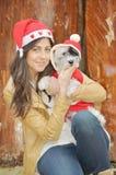 Kobieta ściska jej psa ubierał z czerwonymi boże narodzenie kapeluszami Zdjęcia Royalty Free