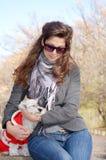 Kobieta ściska jej psa ubierał z czerwonymi boże narodzenie kapeluszami Fotografia Royalty Free