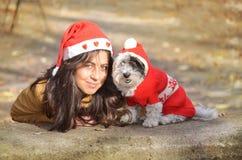 Kobieta ściska jej psa ubierał z czerwonymi boże narodzenie kapeluszami Fotografia Stock