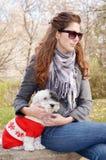 Kobieta ściska jej psa ubierał z czerwonymi boże narodzenie kapeluszami Zdjęcie Royalty Free