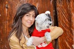 Kobieta ściska jej psa ubierał z czerwonymi boże narodzenie kapeluszami Obraz Royalty Free