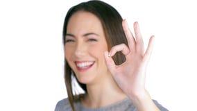 Kobieta śmia się gestykulujący ok szyldowy odosobnionego na bielu zdjęcie wideo
