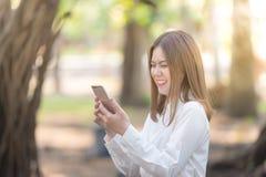Kobieta śmiech i ono uśmiecha się z mądrze telefonem Zdjęcia Stock