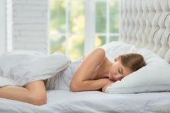 Kobieta śpi na białym łóżku Zdjęcie Royalty Free