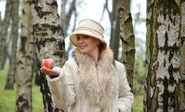 Kobieta średni rok utrzymania w kapeluszu na palmowym dekoracyjnym jabłku zdjęcie stock