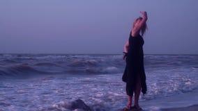 Kobieta żartuje, śmiający się, błaź się wokoło, mieć zabawę, macha ona ręki podczas gdy stojący na kamieniu w falach zdjęcie wideo