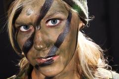 Kobieta żołnierz z kamuflaż twarzą wewnątrz fotografia royalty free