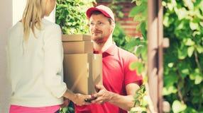 Kobieta akceptuje domową dostawę pudełka od deliveryman obraz stock