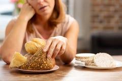 Kobieta alergiczna gluten bierze małą babeczkę z ziarnami zdjęcia stock
