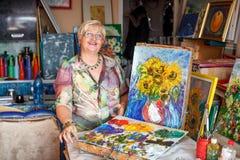 Kobieta artysta blisko obrazu olejnego obrazka w studiu Fotografia Stock