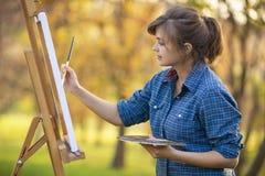 Kobieta artysta rysuje obrazek na sztaludze w naturze, dziewczynie z, pojęciu twórczość i hobby, muśnięciem i paletą, obraz royalty free