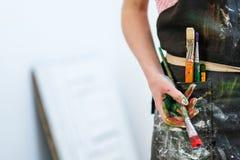 Kobieta artysty ręka z czerwoną farbą i muśnięciem Czarny fartuch, biały tło zdjęcie royalty free