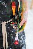 Kobieta artysty ręka z czerwoną farbą i muśnięciem Czarny fartuch, biały tło obraz stock