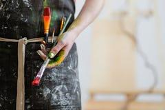 Kobieta artysty ręka z czerwoną farbą i muśnięciem Czarny fartuch, biały tło obraz royalty free