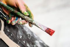 Kobieta artysty ręka z czerwoną farbą i muśnięciem Czarny fartuch, biały tło fotografia stock