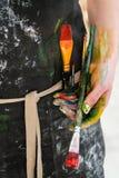Kobieta artysty ręka z czerwoną farbą i muśnięciem Czarny fartuch, biały tło zdjęcie stock