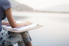 Kobieta artysty rysunek coś przy brzeg rzeki Fotografia Royalty Free