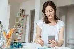 Kobieta artysty rysunek i używać smartphone w warsztacie Zdjęcia Stock
