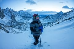 Kobieta arywista w hełma i puszka kurtce z trekking kijami iść ciężkim przy świtem Obraz Royalty Free