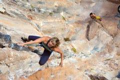 Kobieta arywisty obwieszenie na pionowo Skalistej ścianie jej partnera dopatrywanie up i Zdjęcie Stock