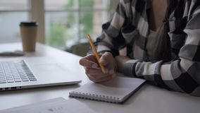 Kobieta autora writing wewnątrz inwestuje notatnika, pracuje przy biurkiem z laptopem w ministerstwie spraw wewnętrznych zdjęcie wideo