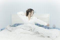 kobieta azjatykcia piękna słuchająca muzyka Słuchający Muzyczny hełmofonu pojęcie Atrakcyjna azjatykcia kobieta budzi na łóżku, s zdjęcia stock