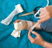 Kobieta bandażuje jej zdradzoną nogę Zdjęcie Royalty Free