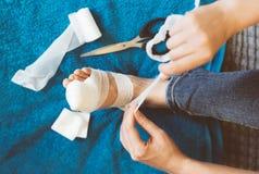 Kobieta bandażuje jej zdradzoną nogę Fotografia Stock