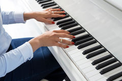 Kobieta bawić się białego pianino Zdjęcia Stock