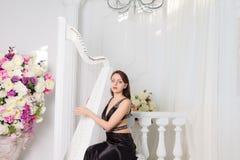 Kobieta bawić się harfę w klasycznym koncercie Obrazy Stock