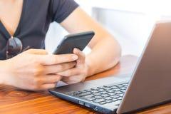 Kobieta bawić się mądrze telefon z laptopem umieszczającym w przodzie Fotografia Stock