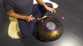 Kobieta bawić się medytacyjnego instrumentu cysternowego bęben w ciemnym medytacja pokoju zbiory