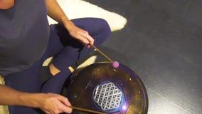 Kobieta bawić się medytacyjnego instrumentu cysternowego bęben w ciemnym medytacja pokoju zdjęcie wideo