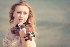 Kobieta bawić się skrzypce na skrzypcowej pobliskiej plaży Zdjęcie Royalty Free