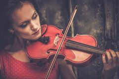 Kobieta bawić się skrzypce w tajemniczym wnętrzu Zdjęcie Royalty Free