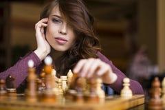Kobieta bawić się szachową salowej i główkowania pozycję, znaleziska wygrania ruch, strategia zdjęcia stock