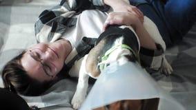 Kobieta bawić się z psem na łóżku zdjęcie wideo