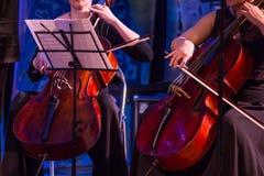 Kobieta bawić się wiolonczelę w orkiestrze zdjęcia royalty free