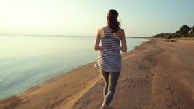 Kobieta bieg na plaży przy zmierzchem zbiory