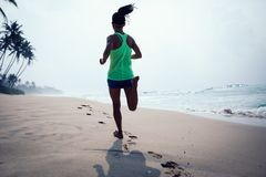 Kobieta bieg na tropikalnej plaży podczas wschód słońca obraz stock