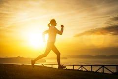 Kobieta bieg w kierunku morza na zmierzchu Fotografia Royalty Free