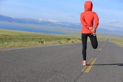 Kobieta biegacz grże up na wiejskiej drodze Zdjęcie Royalty Free
