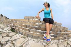 Kobieta biegacz siedzi na wielkim murze Zdjęcie Royalty Free