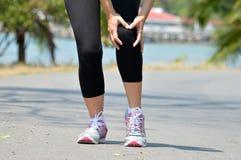 Kobieta biegacz trzyma ona sport raniący kolano zdjęcie royalty free