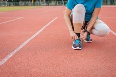 Kobieta biegacz wiąże shoelace na bieg śladzie, atleta wiązać ona buty zdjęcia royalty free