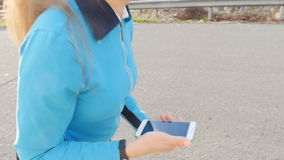 Kobieta biegacza atleta używa jej mądrze zegarek zbiory
