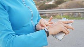 Kobieta biegacza atleta używa jej mądrze zegarek zdjęcie wideo