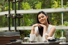 Kobieta bielu skrótu suknia siedzi w Zielarskiej restauracji zdjęcia stock